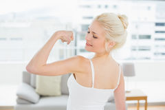 Rear view of fit woman flexing muscles in fitness studio Royalty Free Stock Image