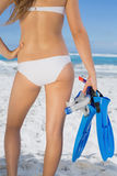 Rear view of fit woman holding fins and snorkel on the beach Royalty Free Stock Image