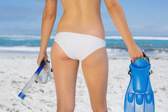 Rear view of fit woman holding fins and snorkel on the beach Stock Photography