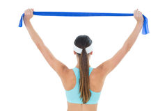 Rear view of a fit woman holding up a yoga belt Royalty Free Stock Photo