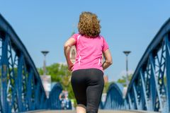 Rear view of a fit woman jogging across a bridge. Rear view of a fit woman jogging across a blue arched bridge in urban environment conceptual of a healthy stock photography