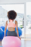 Rear view of a fit woman sitting on fitness ball at gym Stock Photos