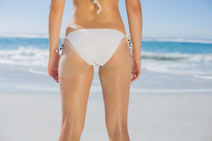 Rear view of fit woman in white bikini on beach. On a sunny day Stock Photo