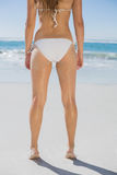 Rear view of fit woman in white bikini on beach. On a sunny day Royalty Free Stock Photos