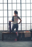 Rear view of fit woman with yoga mat looking out loft gym window Royalty Free Stock Photos