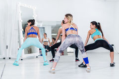 Rear view of fit young girls practicing twerk movements in dancing workshop.  Royalty Free Stock Image