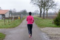 Rear view of a fit young woman jogging. Along a rural road in winter on a grey day in a healthy lifestyle and fitness concept Royalty Free Stock Photography