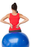 Rear view of a fit young woman sitting on exercise ball Royalty Free Stock Photos