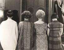 Rear view of four women standing in a row stock images