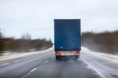 Rear view at freight truck driving on slippery winter highway, northern forest route, blured roadside Stock Image