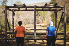 Rear view of friends looking at monkey bar during obstacle course. In boot camp Stock Photography