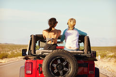 Rear View Of Friends On Road Trip Driving In Convertible Car Stock Image