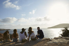 Rear View Of Friends Sitting On Cliff Watching Sunset Royalty Free Stock Photography