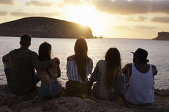 Rear View Of Friends Sitting On Cliff Watching Sunset Stock Photo