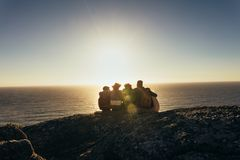 Friends admiring the sunset from mountain top Stock Photo