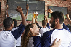 Rear View Of Friends Watching Game In Sports Bar On Screens Royalty Free Stock Photos
