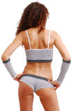 Rear view of frizzy girl in polka dot clothes. Pretty woman is standing back. The frizzy girl is wearing sexy shorts and top. Her neat body is accentuated with Royalty Free Stock Photography