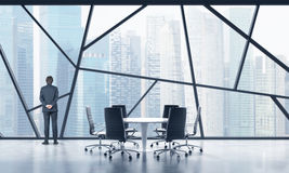 Rear view of a full length man in a formal suit who is looking out the window in a modern panoramic meeting room in Singapore. The Stock Photos