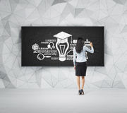 Rear view of full-length student who is presenting educational concept on the black chalk board. Stock Image