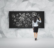 Rear view of full-length woman who is drawing business icons on the black board. Stock Photo