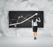 Rear view of full-length woman who is presenting growing line graph on the black board. Royalty Free Stock Photo