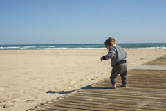 Rear view full shot baby boy walking in the beach. Royalty Free Stock Photos