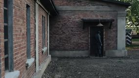 Back view of a German soldier going to a door of a one-story red brick building, knocking at it, turning around, and. Rear view of a German soldier with a rifle stock video