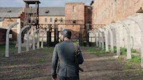 Rear view of a German soldier with a rifle marching. Death camp on the background. WWII reconstruction. Back close view of an actor dressed as a German soldier stock footage