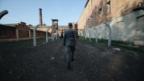 Back view of a male actor dressed as a German soldier walking outside on the territory of a concentration camp
