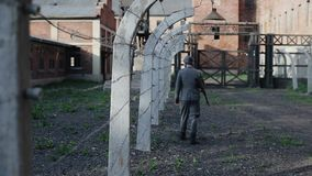 Rear view of a German soldier walking along a barb wire fence guarding a concentration camp. Reenactment of WWII. Back view of a male actor dressed as a German stock video