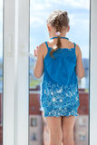 Rear view of girl in blue dress standing behind window glass Royalty Free Stock Photography