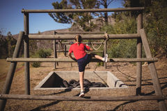 Rear view of girl climbing outdoor equipment during obstacle course. In boot camp stock photography