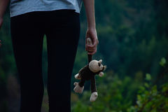 Rear view of girl, close up of hands of a female child holding a monkey toy. Girl standing holding a brown furry monkey toy. Royalty Free Stock Image