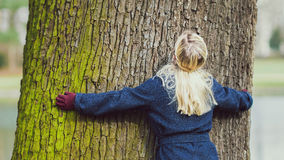 Rear view on girl with curly hair embracing a tree. Rear view on girl with blond curly hair embracing, hug a tree Royalty Free Stock Photo