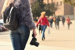 Rear view of a girl with a digital camera on a crowded street ba royalty free stock images