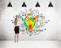 Rear view of girl drawing bright light bulb Royalty Free Stock Image