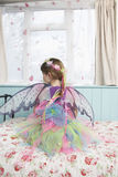 Rear View Of Girl In Fairy Costume Sitting On Bed. Rear view of a young girl in fairy costume sitting on bed looking through window Stock Image