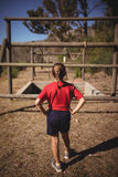 Rear view of girl looking at outdoor equipment during obstacle course. In boot camp royalty free stock photo