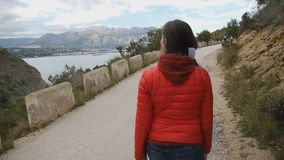 Rear view of a girl in red bubble jacket walking on a mountain road on the sea and mountain landscape background. Rear view of a girl in red bubble jacket stock video