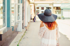 Rear view of a girl with red hair in a black hat walking around the city. Sunny summer day. City style.Girl wearing stylish summer. Dress of lace Stock Image