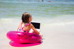 Rear view of girl sitting on beach with laptop Royalty Free Stock Images