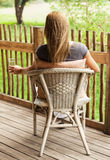 Rear view of girl sitting on veranda Stock Image
