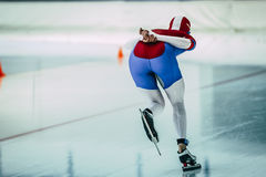 Rear view girl speed skaters goes on ice stadium Stock Photo