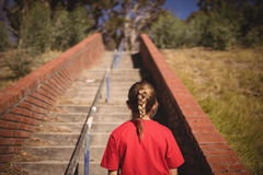 Rear view of girl standing near staircase during obstacle course. In boot camp stock images