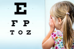 Rear view of girl testing eyesight. Close up rear view of girl testing eyesight. Infant closing one eye with hand looking at vision test chart Royalty Free Stock Photography
