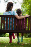 Rear view of girl and woman sitting on wooden bench Royalty Free Stock Photos