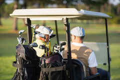 Rear view of golfer friends sitting in golf buggy Stock Images