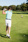 Rear view of golfer man taking shot. While standing on field royalty free stock images