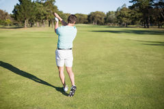 Rear view of golfer taking shot. While standing on field stock images
