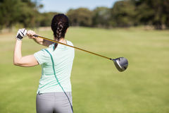 Rear view of golfer woman taking shot Royalty Free Stock Image